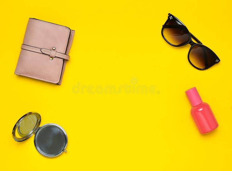 Accessori femminili su un fondo giallo Prodotti per bellezza e modo Occhiali da sole, borsa, bottiglia di profumo fotografia stock libera da diritti