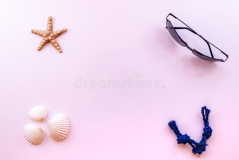 Accessori per estate con gli occhiali da sole, le conchiglie e le stelle marine su fondo rosa, fotografia posta piana creativa, v fotografia stock