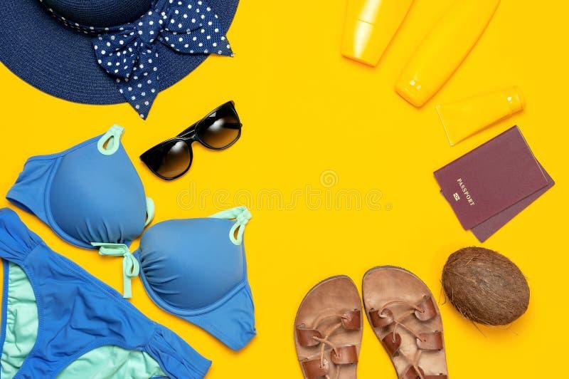 Accessori per il vestiario femminili di estate su fondo giallo Concetto del mare di vacanza di viaggio Sandali di cuoio blu del v fotografia stock libera da diritti