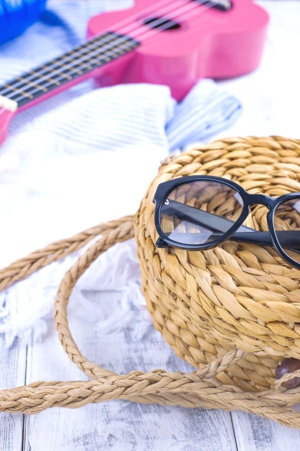 Accessori per la spiaggia, la chitarra e la borsa fatte di paglia Buone vacanze Copi lo spazio immagine stock