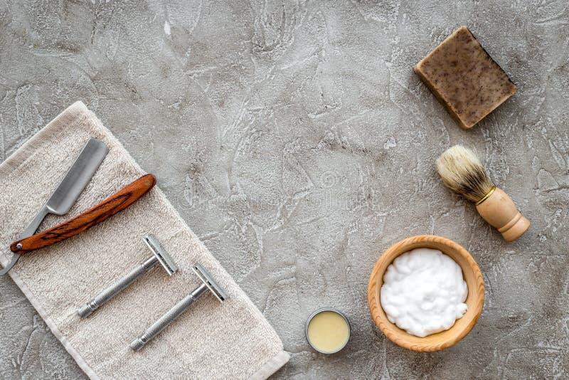 Accessori per radersi Spazzola di rasatura, rasoio, schiuma sul copyspace di pietra grigio di vista superiore del fondo della tav immagini stock libere da diritti