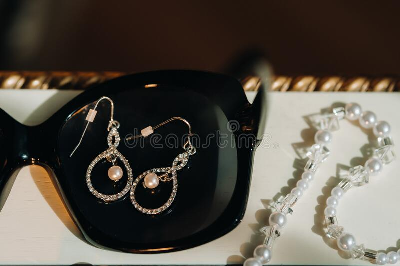 Accessories for the bride. Earrings on a black background. White wedding earrings. Space for text and ads.  stock photography