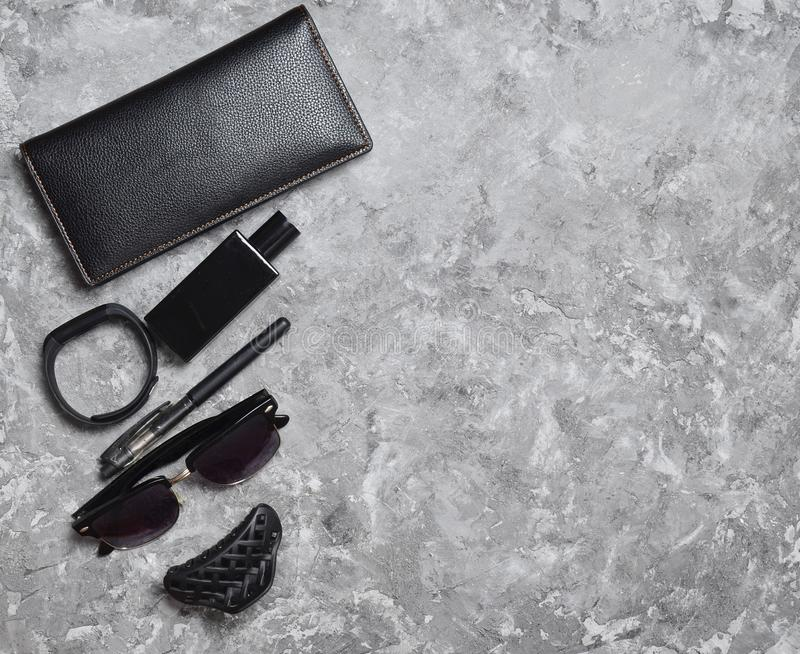 Accessories for a business woman on a concrete table. Purse, perfume, sunglasses, smart watch, pen. Working space. Monochrome photography. Trend of minimalism royalty free stock image