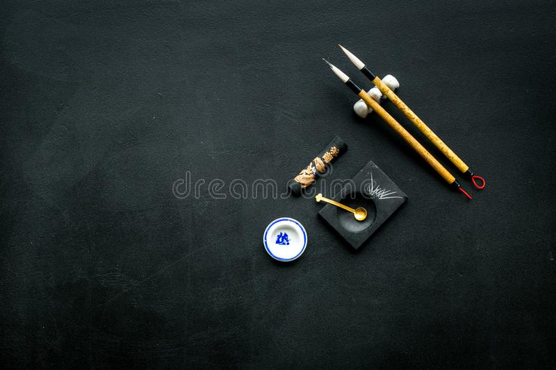 Accessories for chinese or japanese calligraphy. Special writting pen, ink on black background top view copy space. Accessories for chinese or japanese royalty free stock photo