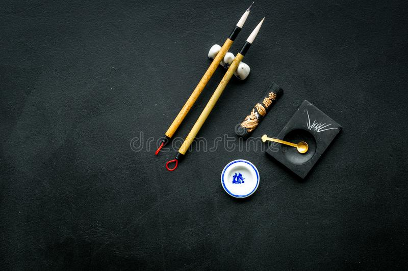 Accessories for chinese or japanese calligraphy. Special writting pen, ink on black background top view copy space. Accessories for chinese or japanese stock photo