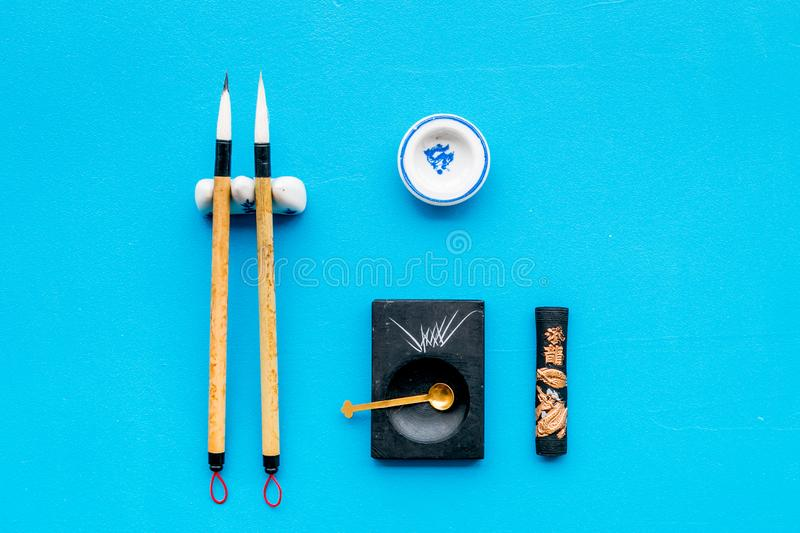 Accessories for chinese or japanese calligraphy. Special writting pen, ink on blue background top view copy space. Accessories for chinese or japanese stock image