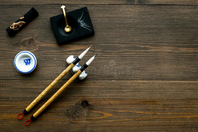 Accessories for chinese or japanese calligraphy. Special writting pen, ink on dark wooden background top view space for. Accessories for chinese or japanese royalty free stock images