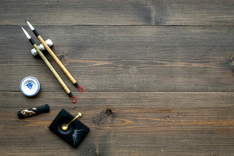 Accessories for chinese or japanese calligraphy. Special writting pen, ink on dark wooden background top view space for. Accessories for chinese or japanese stock photos