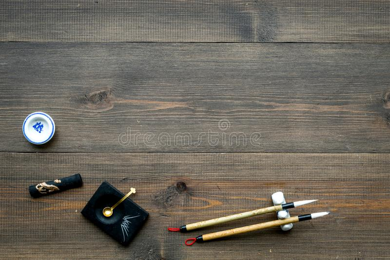 Accessories for chinese or japanese calligraphy. Special writting pen, ink on dark wooden background top view space for. Accessories for chinese or japanese stock image