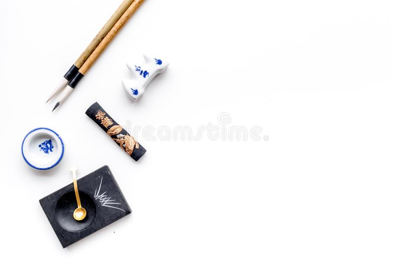 Accessories for chinese or japanese calligraphy. Special writting pen, ink on white background top view copy space. Accessories for chinese or japanese stock photography