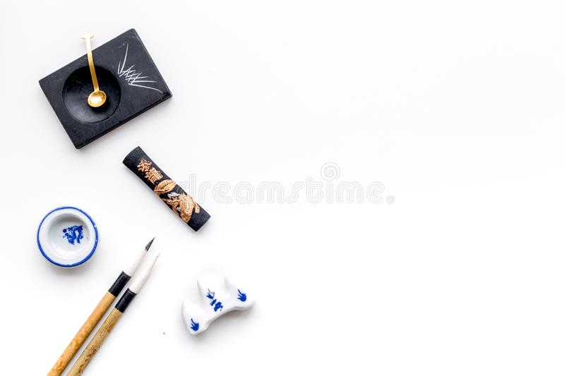 Accessories for chinese or japanese calligraphy. Special writting pen, ink on white background top view copy space. Accessories for chinese or japanese stock photos