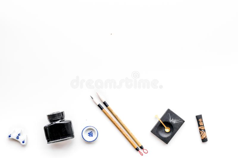 Accessories for chinese or japanese calligraphy. Special writting pen, ink on white background top view space for text. Accessories for chinese or japanese royalty free stock photo