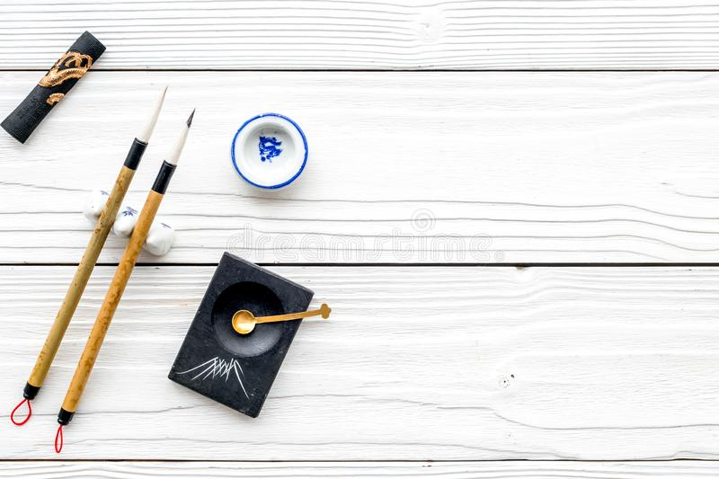 Accessories for chinese or japanese calligraphy. Special writting pen, ink on white wooden background top view copy. Accessories for chinese or japanese stock photo