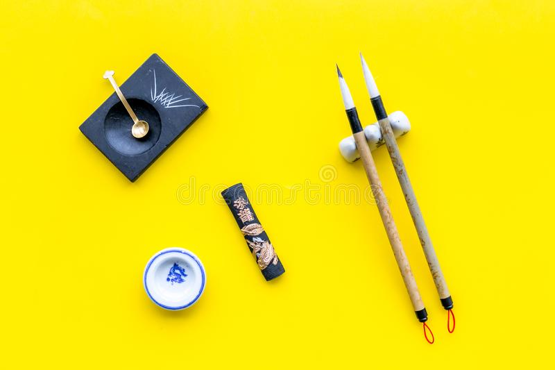 Accessories for chinese or japanese calligraphy. Special writting pen, ink on yellow background top view.  stock images