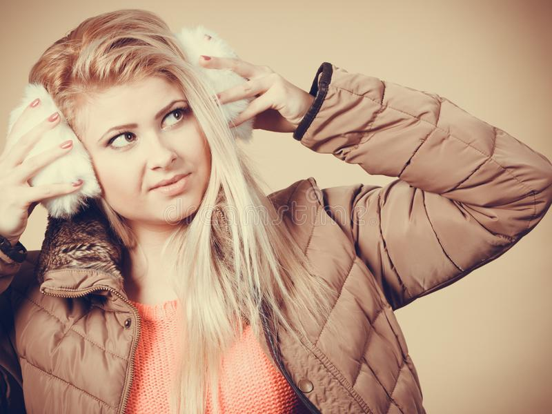 Blonde woman in winter earmuffs and jacket stock image