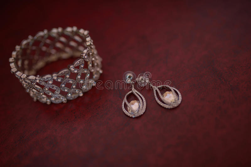 Thick semi-precious bracelet and matching hanging earrings displayed on a dark, burgundy mat royalty free stock photo