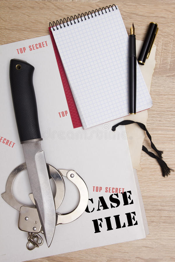 Accessories detective. Folder affairs and notepad, pen and handcuffs, a knife from the scene royalty free stock images