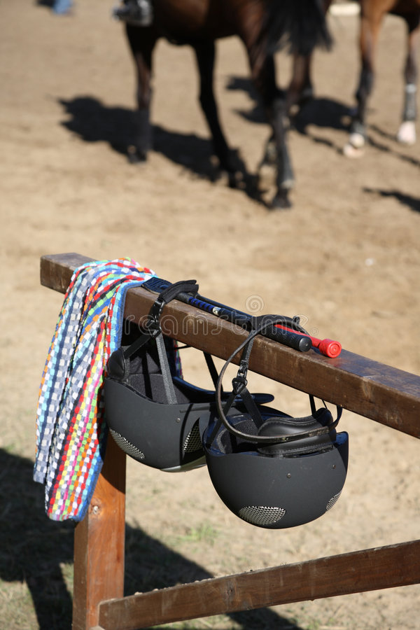 Accessories for show jumping. Two helmets, two whips- two friends, two rivals stock image