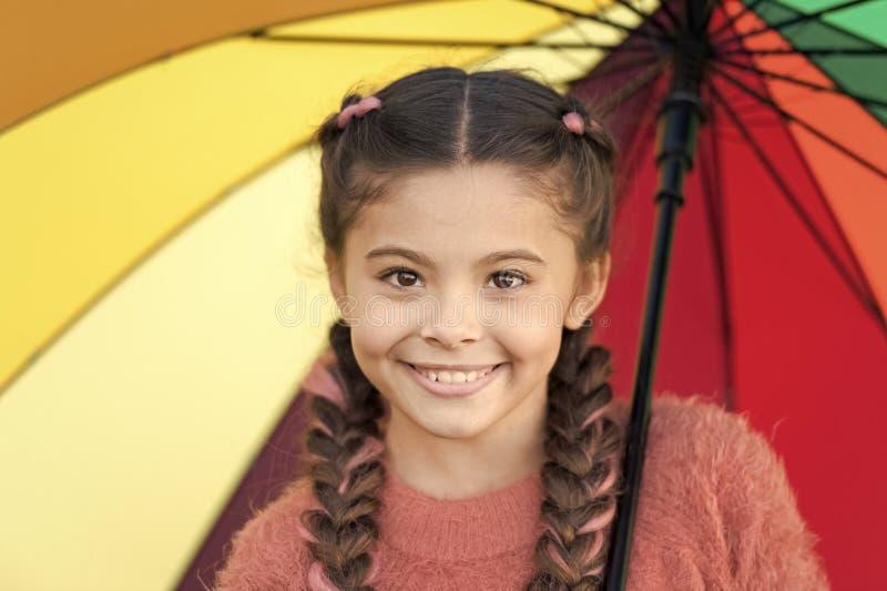 Accessorio variopinto per l'umore allegro Capelli lunghi del bambino della ragazza che camminano con l'ombrello Soggiorno positiv fotografia stock