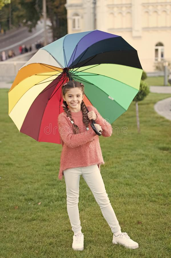 Accessorio variopinto per l'umore allegro Parco di camminata dei capelli lunghi del bambino della ragazza con l'ombrello Soggiorn immagini stock libere da diritti
