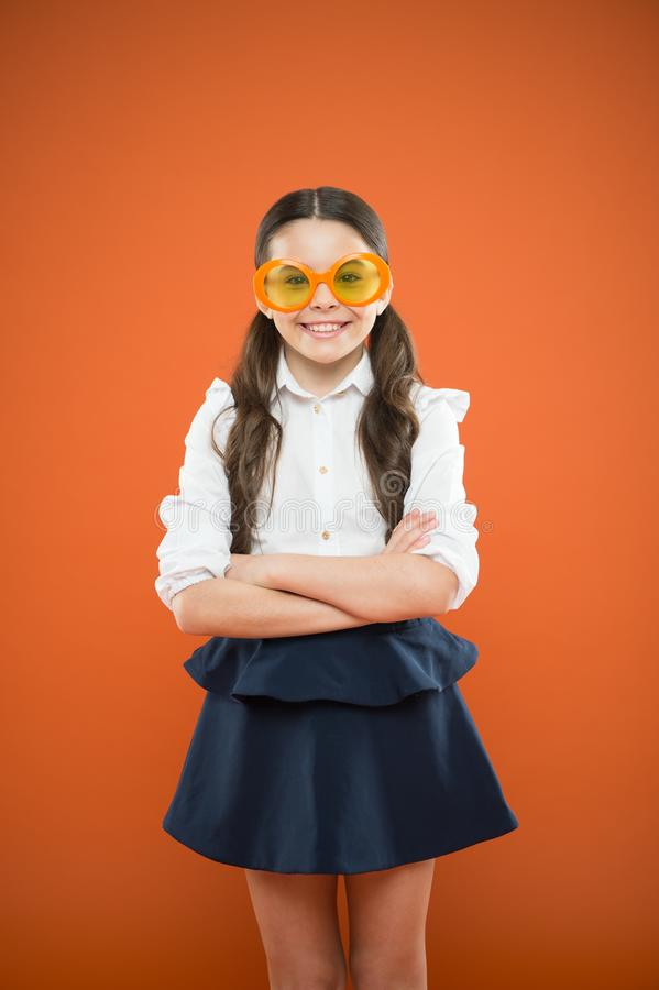 Accessory far too stylish to take off. Small kid smiling in fancy accessory on orange background. Happy girl wearing eye stock photography