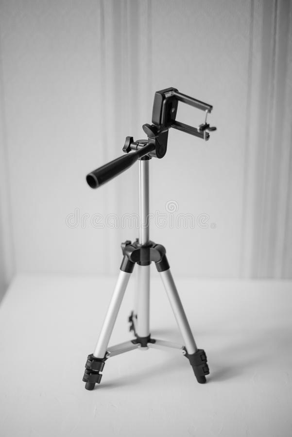 Accessory for the phone: partially spread out tripod for a smartphone on the table on the background of wallpaper, black and white royalty free stock images
