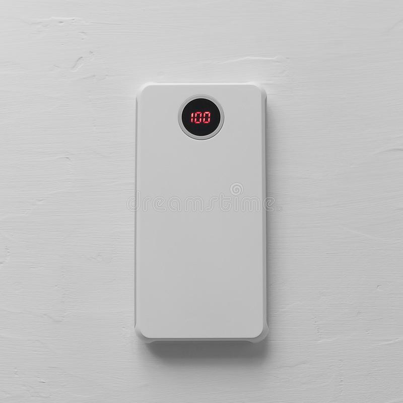 Accessory for your phone: power bank for a white smartphone with a charge sensor on a white textural background top view royalty free stock photos