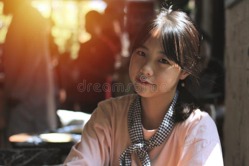 Acción asiática de la muchacha con los cubiertos mientras que espera la torta imágenes de archivo libres de regalías
