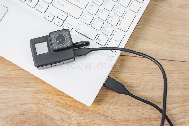 Acción-cámara conectada con un ordenador portátil blanco, contra la perspectiva de una tabla de madera fotos de archivo libres de regalías
