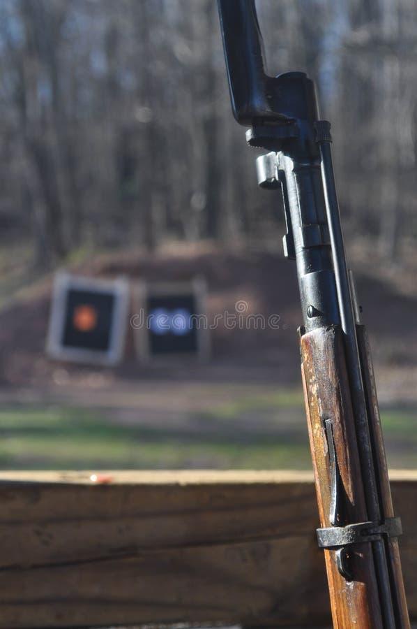 Acción de madera resistida del rifle del arma de Mosin Nagant con la bayoneta atada y blancos en el fondo fotos de archivo