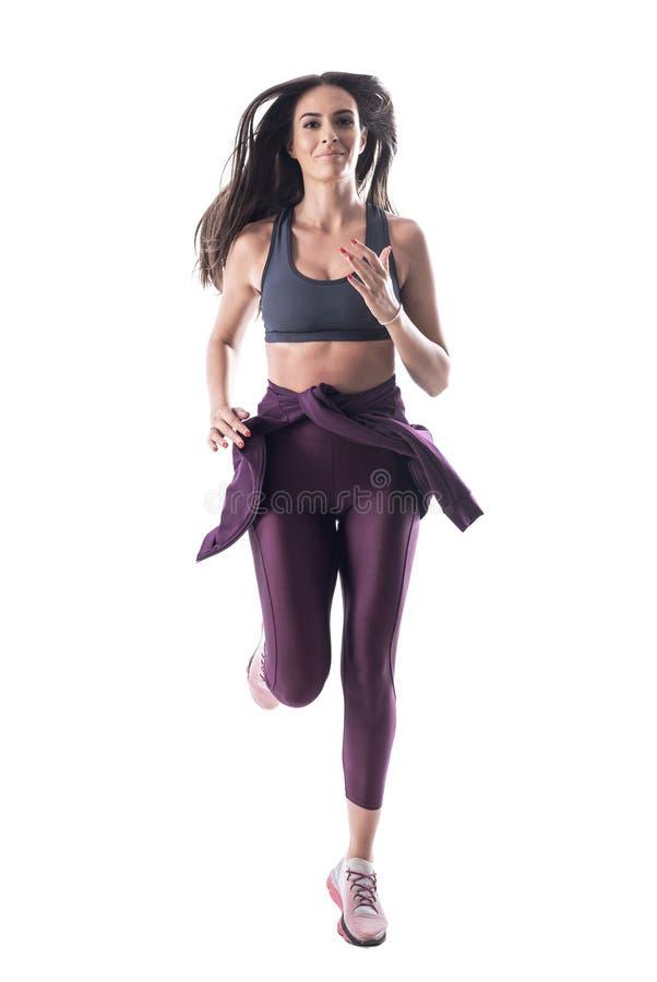 Acción tirada del atleta apto atractivo joven de la mujer que corre y que mira la cámara imagen de archivo libre de regalías