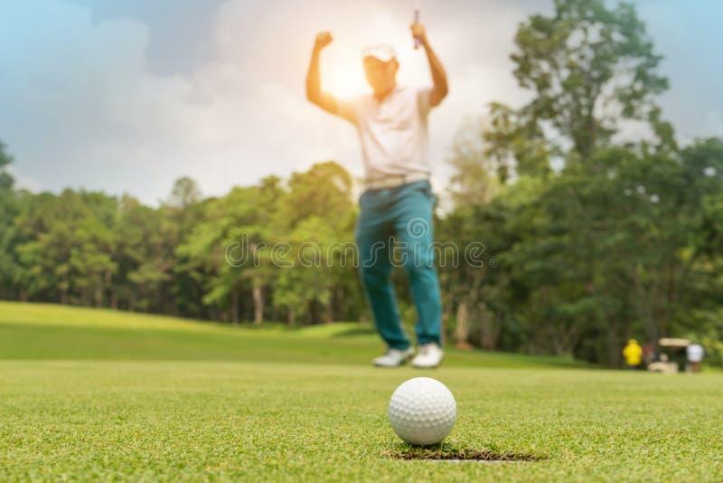 Acci?n del golfista a ganar despu?s de pelota de golf que pone larga en el golf verde fotografía de archivo