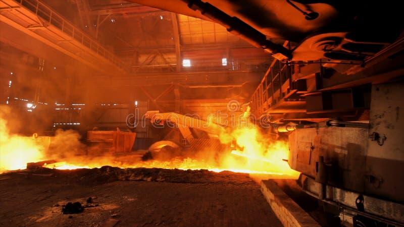 Acciaio caldo che è versato allo scivolo nell'acciaieria, concetto dell'industria pesante Metraggio di riserva Produzione d'accia fotografia stock