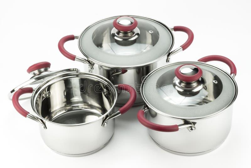 Acciaio inossidabile che cucina i vasi con i coperchi isolati sul backgro bianco fotografie stock