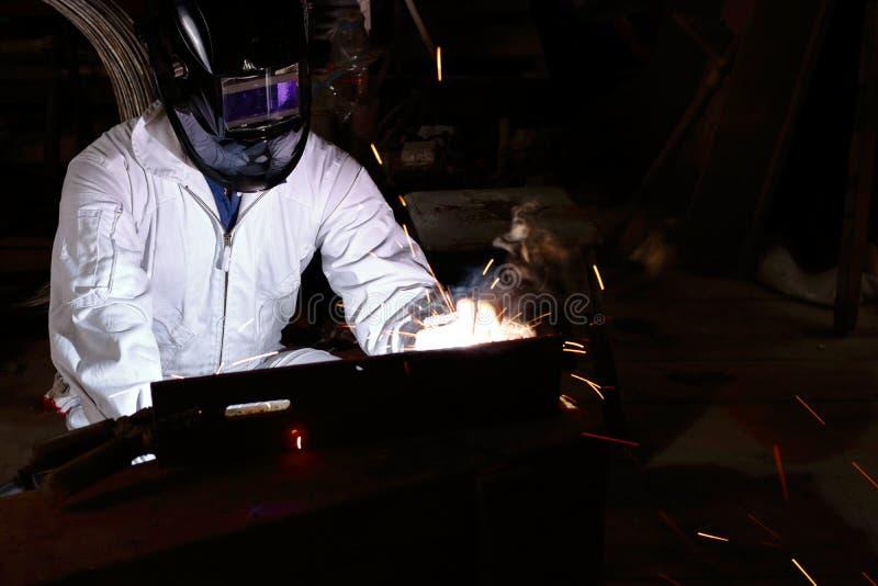 Acciaio professionale della saldatura dell'uomo del saldatore con la scintilla nella fabbrica con il fondo dello spazio della cop immagini stock