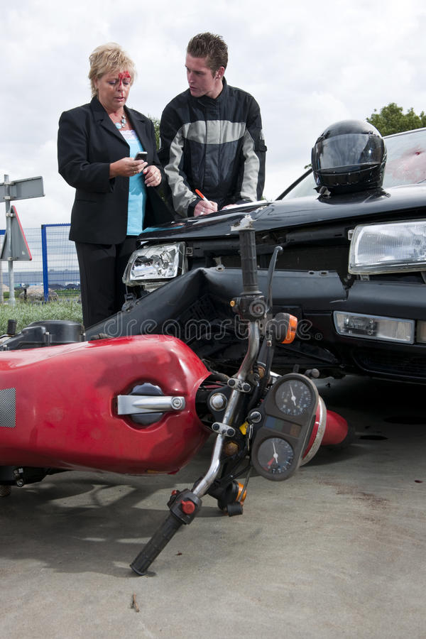 Accident afthermath. The drivers, involved in an accident between a car and a motorcycle, exchanging information for insurance purposes royalty free stock image