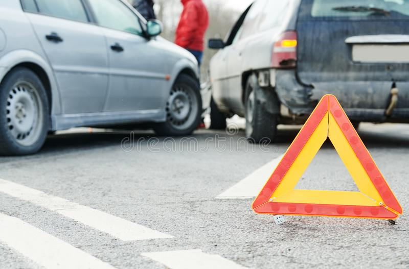 Accident or crash with two automobile. Road warning triangle sign in focus. Car crash in city street. Accident with two automobile. Road warning triangle sign in royalty free stock images