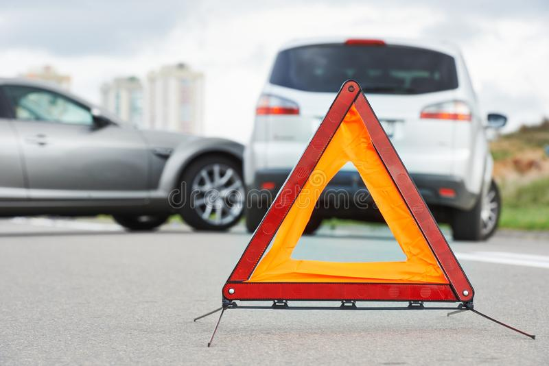 Accident or crash with two automobile. Road warning triangle sign in focus. Car crash in city street. Accident with two automobile. Road warning triangle sign in stock photography