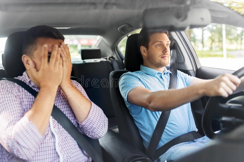 Car driving school instructor and male driver stock photography