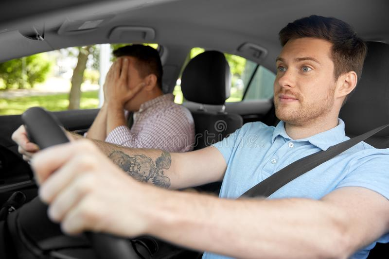 Car driving school instructor and male driver. Accident, emotion and fear concept - scared car driving school instructor and young male driver royalty free stock photo