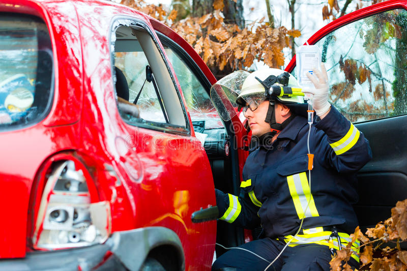 Accident, Fire brigade rescues Victim of a car. Accident - Fire brigade rescues accident Victim of a car, firefighter holds a drip for Infusion royalty free stock photos