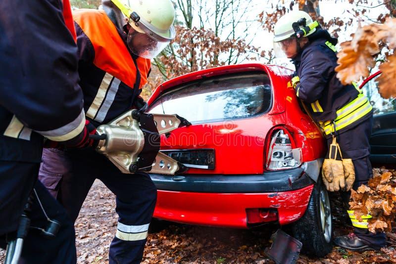 Accident - les sapeurs-pompiers sauvent la victime d'un accident de voiture images libres de droits