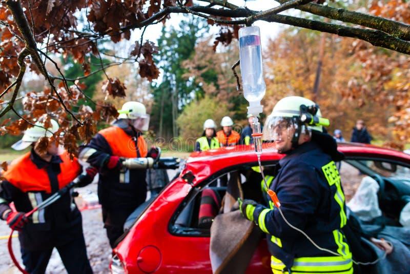 Accident - les sapeurs-pompiers sauvent la victime d'un accident de voiture photos stock