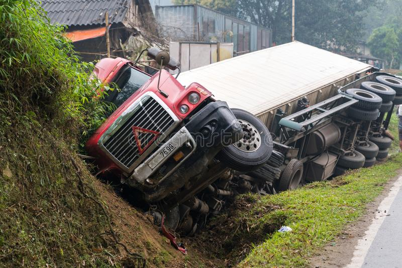 Accident on mountainous road, motor vehicle accident, car wreck. Long vehicle overturned and lying in ditch on side royalty free stock image