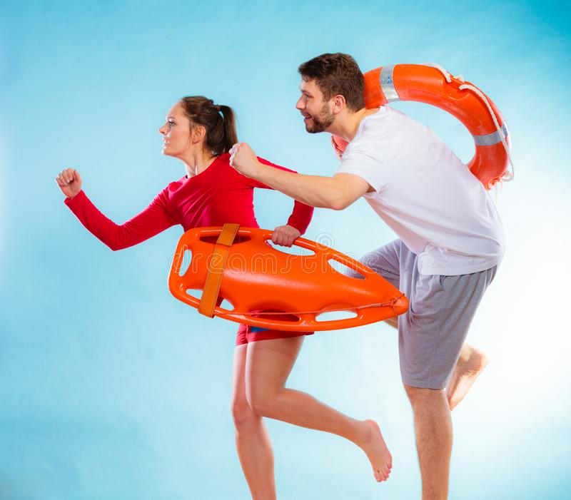 Lifeguards running with equipment. Accident prevention and water rescue. men and women lifeguard couple on duty running with with life belt lifesaver equipment stock photography
