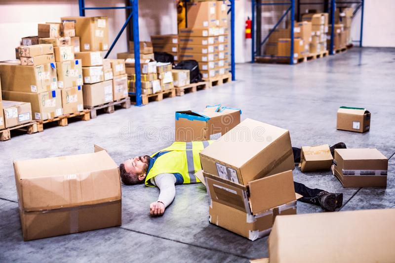 Warehouse worker after an accident in a warehouse. An accident in a warehouse. Man lying on the floor among boxes, unconscious royalty free stock photo