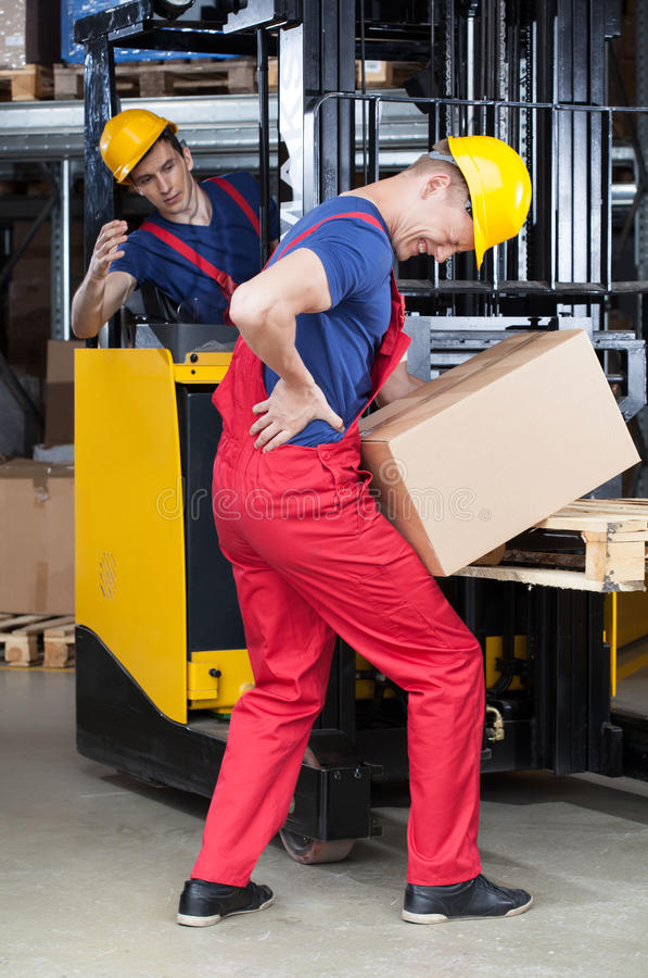 Accident in warehouse during using forklift. Vertical royalty free stock image