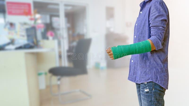 accidente de la mujer del trabajador en el brazo con el molde verde del brazo en busi borroso fotos de archivo libres de regalías