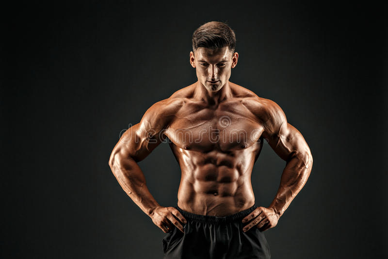 Accidente plano Hombre musculoso de la aptitud en fondo oscuro foto de archivo