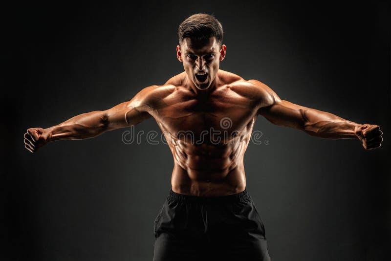 Accidente plano Hombre musculoso de la aptitud en fondo oscuro Rugido para la motivación foto de archivo